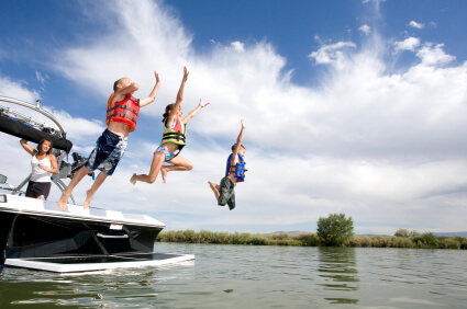 Kids jumping into water off boat